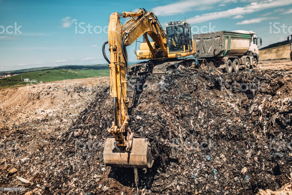 industry details - excavator working on urban trash dumping grounds stock photo