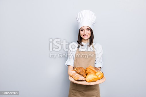 Industry prepare organic natural dough tasty fresh white clothes professional. Portrait of cheerful kind delightful baker demonstrating wooden tray with appetizing food isolated on gray background