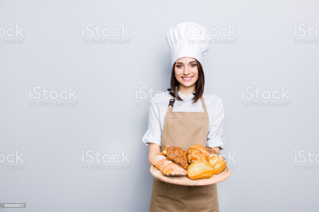 Industry prepare organic natural dough tasty fresh white clothes professional. Portrait of cheerful kind delightful baker demonstrating wooden tray with appetizing food isolated on gray background - fotografia de stock