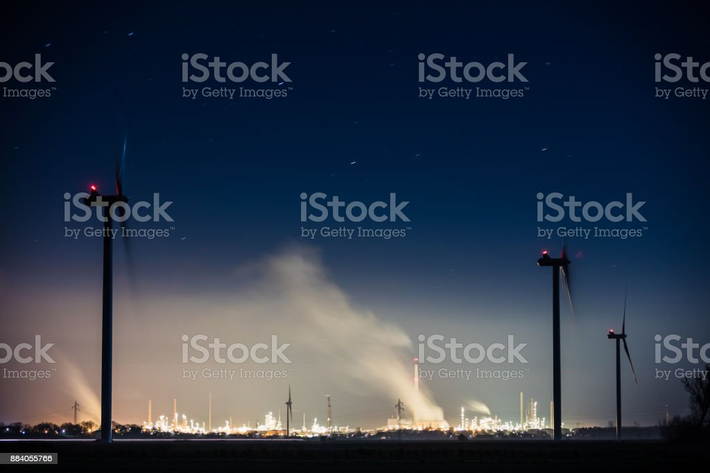 Industry with chimneys and windenergy turbines stock photo
