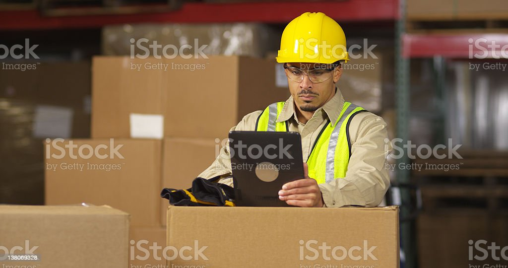 Industry worker using digital tablet in shipping warehouse royalty-free stock photo