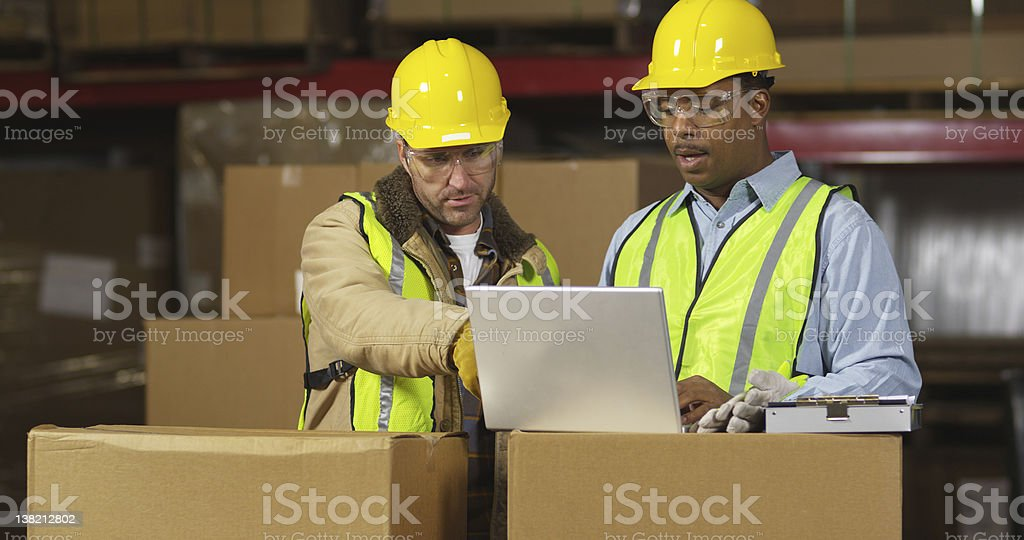 Industry workers look at laptop computer in shipping warehouse royalty-free stock photo