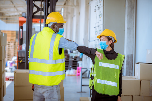 Industry workers under discussion said hello in new normal concept at factory warehouse ,they wearing safety uniform hard hat and medical mask for protect virus
