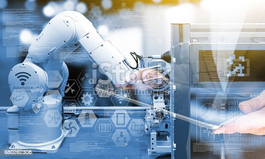 676364668 istock photo Industry4.0 concept .Business man holding tablet with industry graphic sign and blue tone of automate wireless Robot arm in smart factory background. Double exposure , blue tone , flare light 680262308