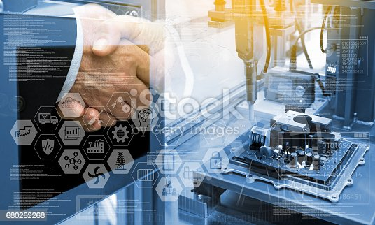 676364668 istock photo Industry4.0 concept .Two Business people shaking hands with industry graphic sign and blue tone of automate wireless Robot arm in smart factory background. Double exposure ,blue tone , flare light 680262268