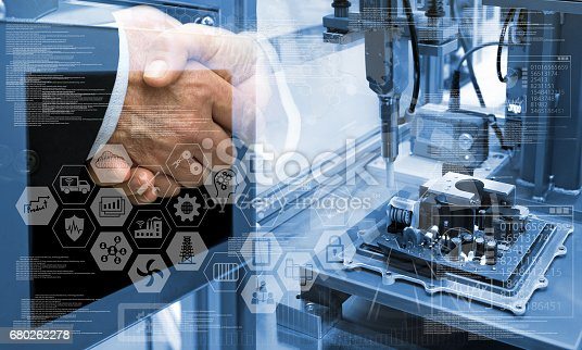 676364668 istock photo Industry4.0 concept .Two Business people shaking hands with industry graphic sign and blue tone of automate wireless Robot arm in smart factory background. Double exposure ,blue tone 680262278