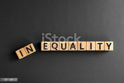 Inequality to equality - word from wooden blocks with letters, economic social inequality concept,  top view on grey background
