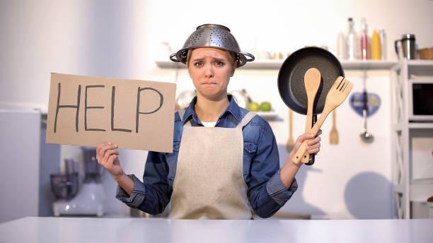 ama de casa inexperta pidiendo ayuda en la cocina, usando hierba en la cabeza, bromea - receta instrucciones fotografías e imágenes de stock