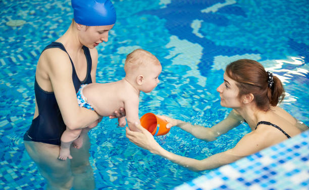 Infant accustoming to water at first lesson in pool. Women entertain and amuse baby to not afraid swimming. Side view Little child accustoming to water at first lesson in pool. Woman entertain and amuse baby to not afraid swimming. Side view. Active family spending leisure and time in spa fitness recreational center amuse stock pictures, royalty-free photos & images
