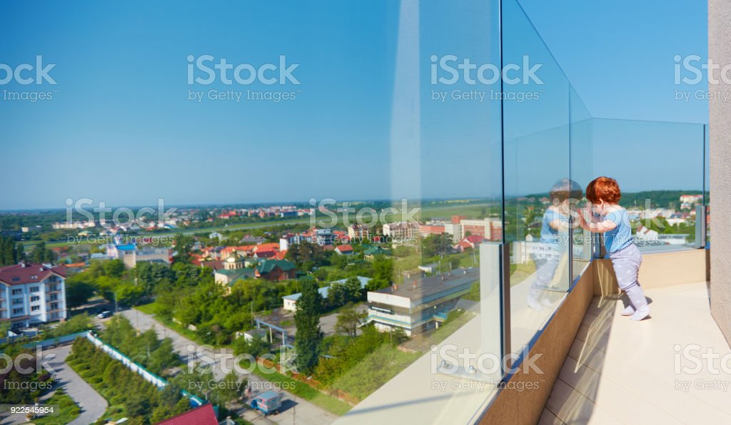 infant baby boy enjoying the city view from the rooftop patio at multi storey building stock photo