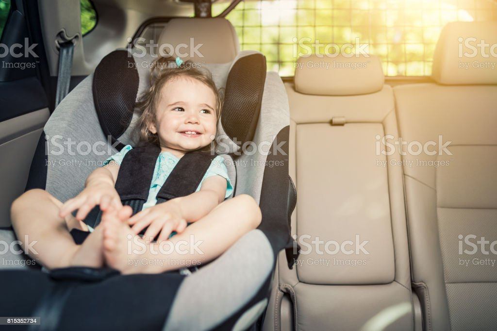 Infant baby girl buckled into her car seat. stock photo