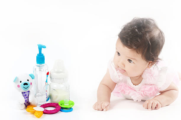 Infant baby girl crawling next essential baby items. stock photo