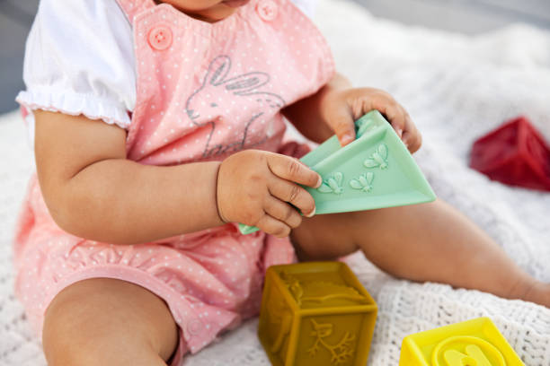 Infant baby girl sitting and playing with colorful rubber blocks on white blanket in the backyard during quarantine stock photo