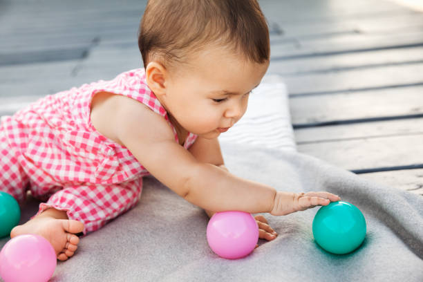 Infant baby girl sitting on wooden floor and playing with colorful plastic balls stock photo