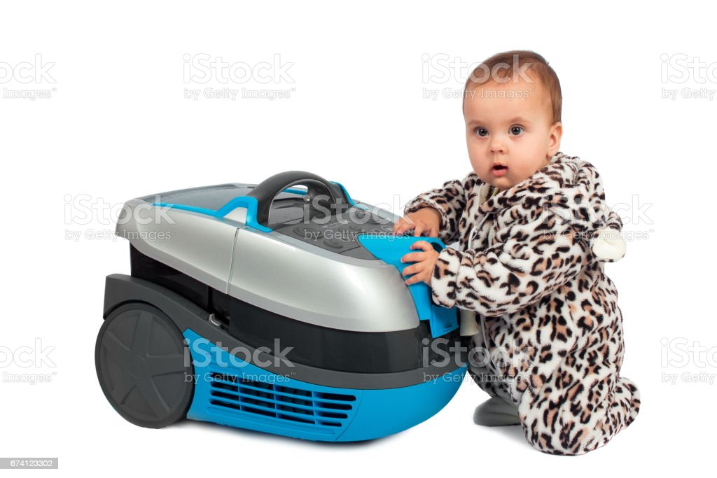 Infant baby sits with vacuum cleaner. Isolated on white background. royalty-free stock photo