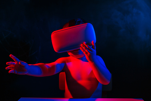 1019302738 istock photo infant baby uses virtual reality VR cardboard isolated on black background. Red blue double color lighting 1019302738