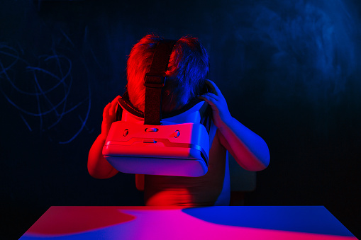 1019302738 istock photo infant baby uses virtual reality VR cardboard isolated on black background. Red blue double color lighting 1019302782