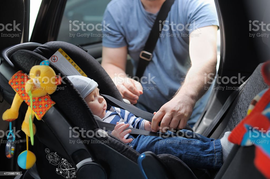 Infant boy in car seat being put in back of car by father stock photo