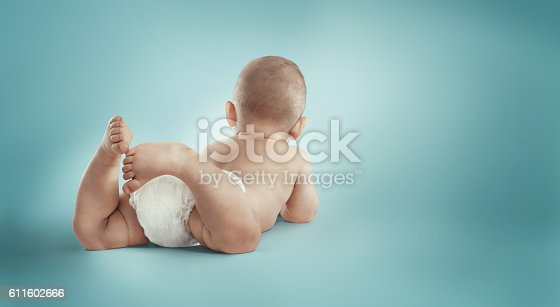 istock Infant child baby toddler laying in diapers. Back view 611602666