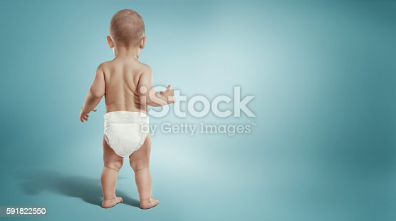 istock Infant child baby toddler standing in diapers. Back view 591822550