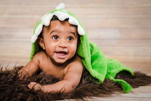 Infant dogla boy wearing bath robe laying on his tummy belly fluffy furry throw wooden background modern studio shoot modern look