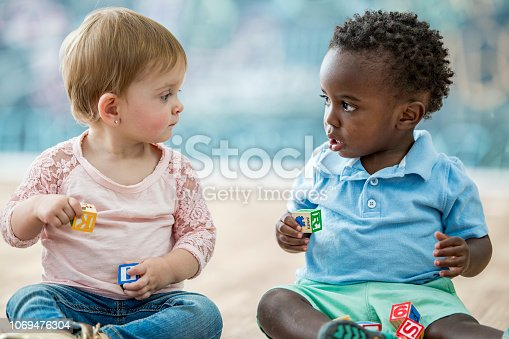 Two infants are sitting and playing with toy blocks in a play room. They are looking at each other.