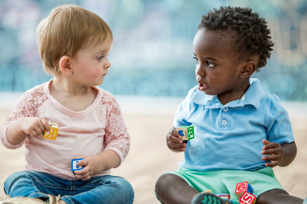 Infant friends Two infants are sitting and playing with toy blocks in a play room. They are looking at each other. preschool student stock pictures, royalty-free photos & images