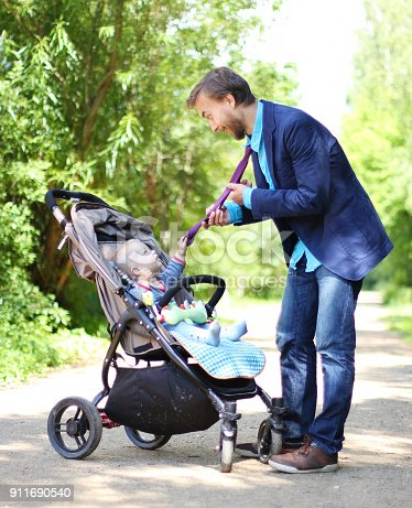 istock infant in a pram holds his father by the tie 911690540