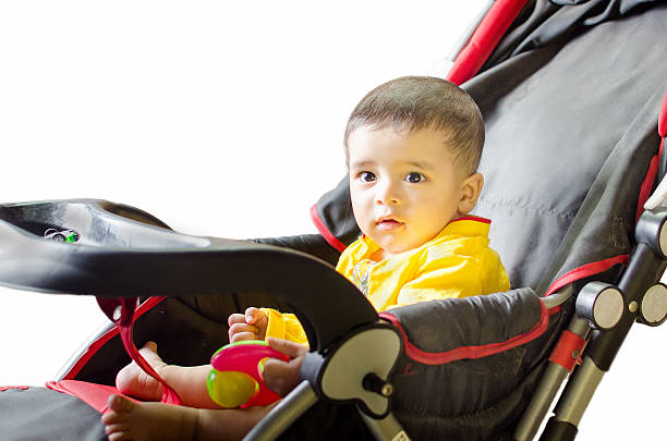 Infant playing on black & red stroller wearing yellow shirt stock photo