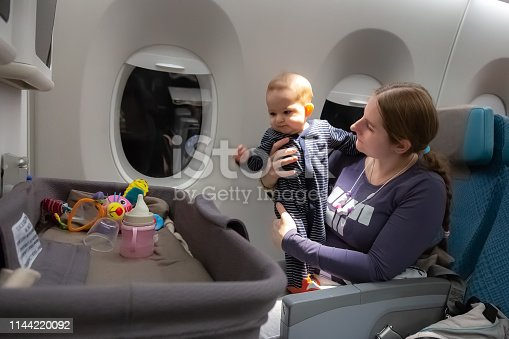 istock Infant plays on mother hands at the airplane.  Interest to special baby bassinet during the flight 1144220092