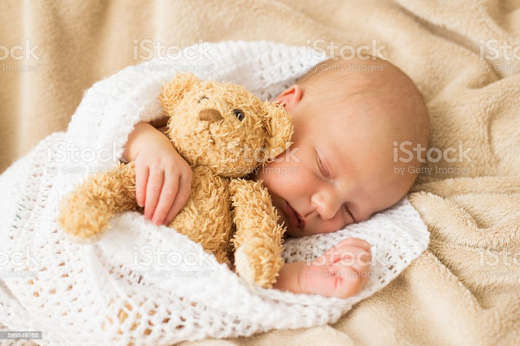 Infant sleeping together with teddy bear stock photo