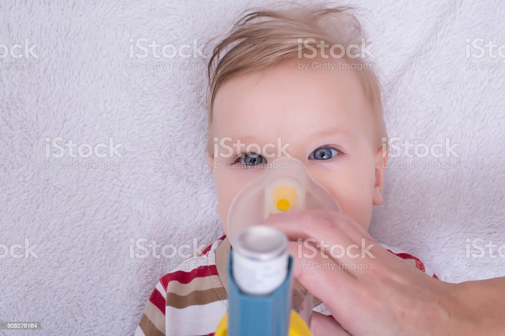 Infant with asthma inhalator stock photo