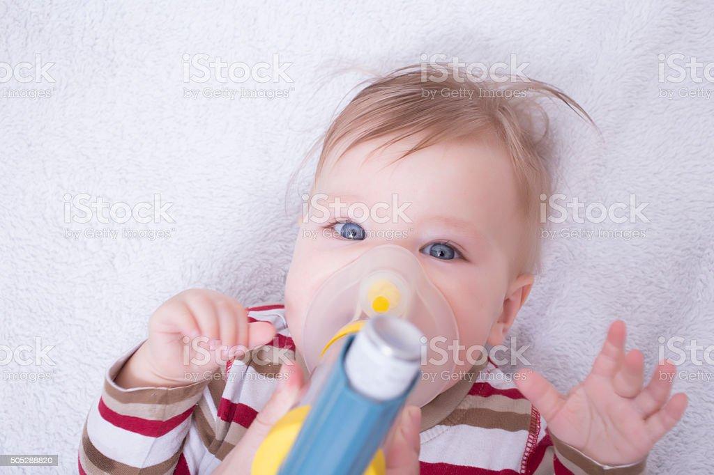 Infant with asthma inhalator stock photo