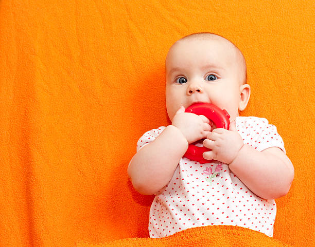 Infant with teething toy stock photo