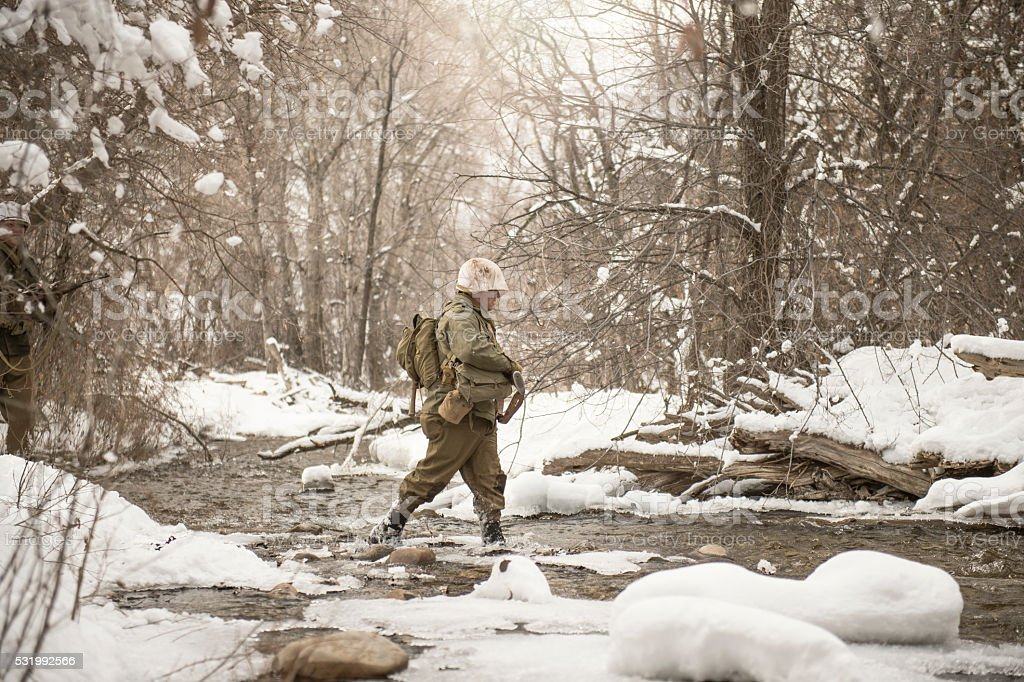 WWII US Infantry Soldier Crossing A Creek In Winter stock photo