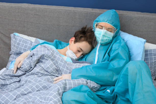 Infected boy patient in quarantine lying in bed, coronavirus concept , Mother and child in home quarantine , quarantine. health concept. Corona Virus. – zdjęcie