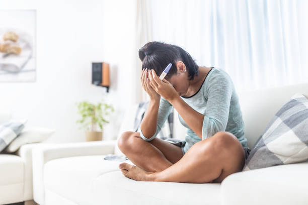 Infertile woman finds out the positive result of her pregnancy test. stock photo