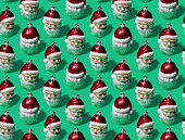 Super high resolution digital image of a repeating pattern of vintage Santa Claus Christmas ornaments on a green background. Image is 100% tileable, and was created as a pattern for gift wrap, backgrounds, cloth, and digital and web applications.