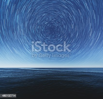 The ocean stretches to the horizon under a canopy of spinning stars.  Earth's axis is revealed at the center.  Composite image.