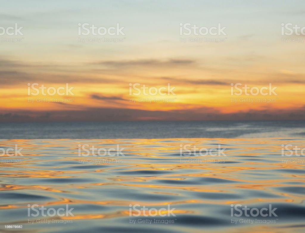 Infinity edge pool with sea underneath sunset royalty-free stock photo