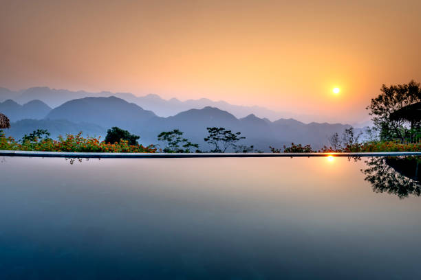 Infinity pool at resort with a view of mountain at beautiful sunrise stock photo