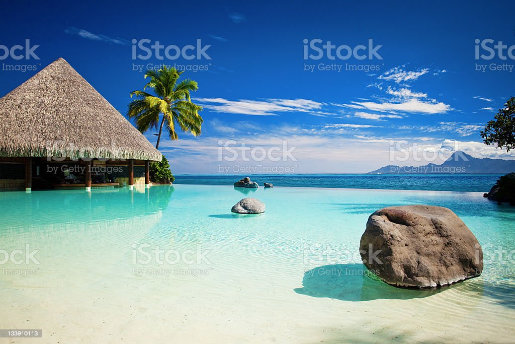 Infinity pool with artificial beach and ocean stock photo