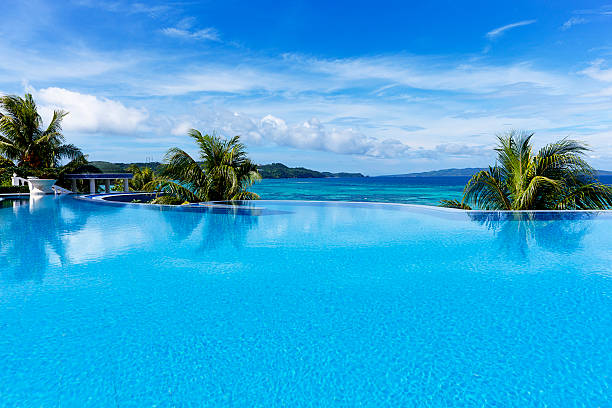 infinity swimming pool beautiful infinity swimming pool in a luxury tourist resort. infinity pool stock pictures, royalty-free photos & images
