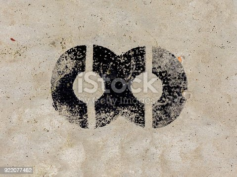 istock Infinity symbol painted black on old rugged concrete light grey wall background 922077462