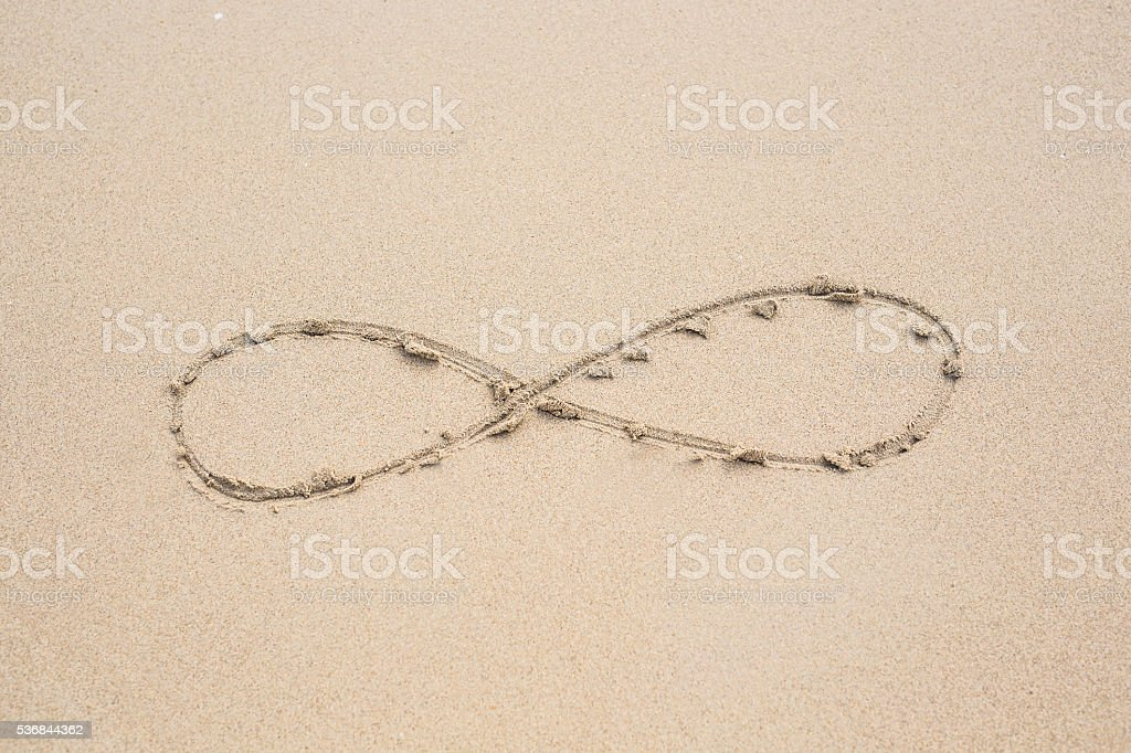 infinity symbol written on sand. stock photo