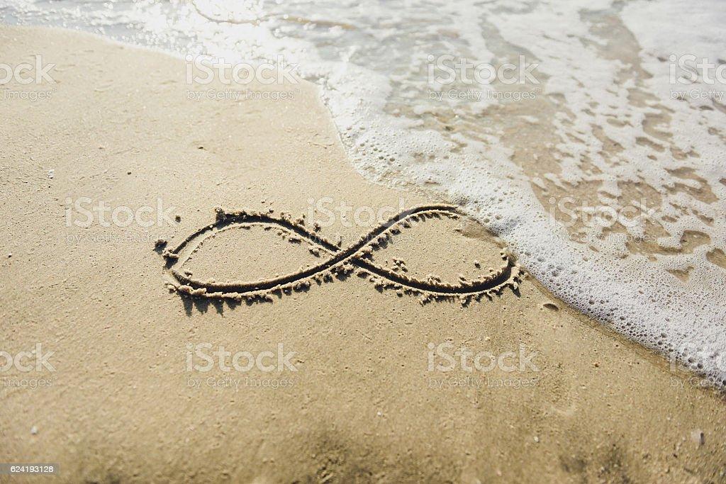 infinity symbol written on sand. stock photo