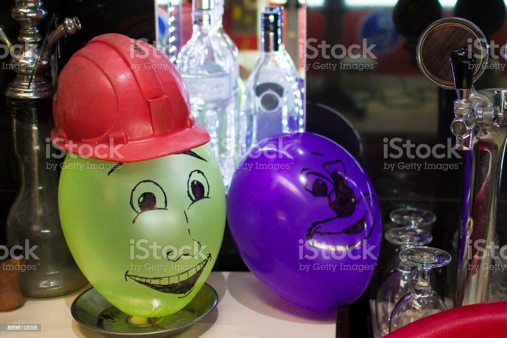 inflatable balls with faces with a helmet in the bar stock photo