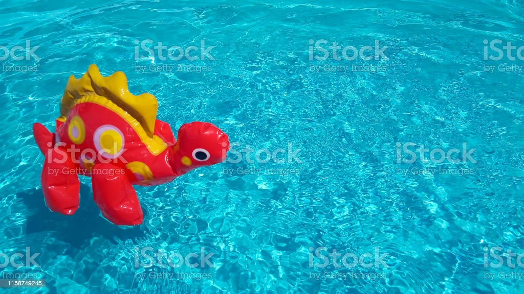 Inflatable dinosaur in clean rippling pool water. Summer vacation...