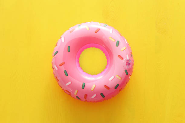 Inflatable donut ring over yellow wooden background – zdjęcie