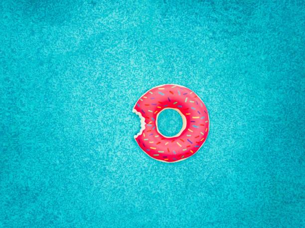 uppblåsbara donut badring i en pool - flotte bildbanksfoton och bilder